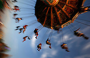 People ride on a swing at the Wisconsin State Fair in West Allis, Wisconsin, August 9, 2014. The fair started over 150 years ago and mixes agricultural exhibits with amusements rides. REUTERS/Jim Young