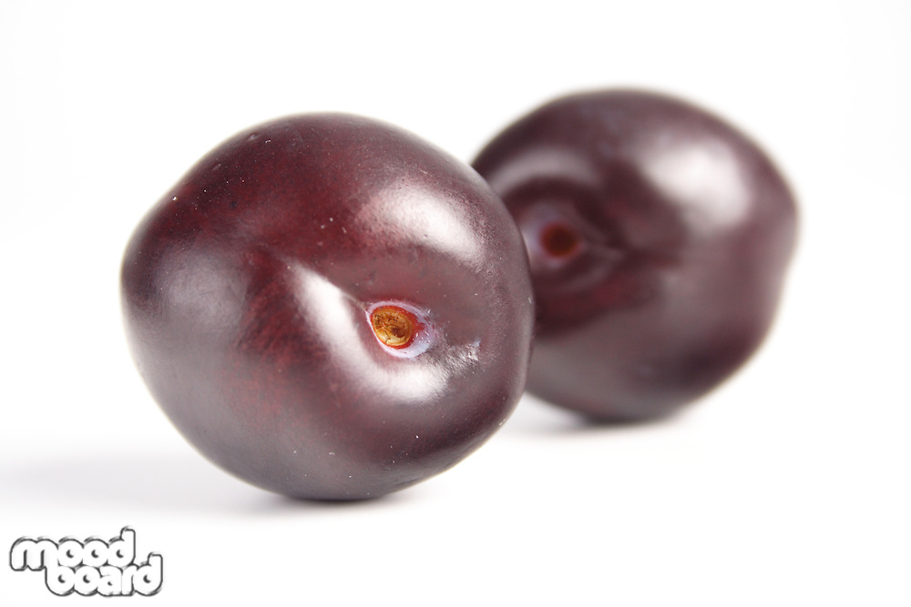 Close-up of plums on white background