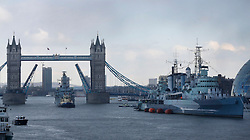 © Licensed to London News Pictures. 13/03/2013, London, UK. A Royal Navy type 23 frigate, HMS Westminster, left, sails through the raised Tower Bridge to moor alongside the HMS Belfast, right, London, Wednesday, March 13, 2013. HMS Westminster is on a six-day visit to London. Photo credit : Sang Tan/LNP