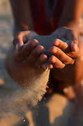 Young woman holds sand in her hands, at sunset