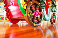 At Nunley's Carousel, colorfully carved chariot riding by, seen from floor level platform in extreme perspective of side and back, at Museum Row, Garden City, New York, USA, on August 7, 2012