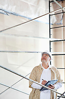 Male architect making a note in digital tablet pc while looking up at construction site