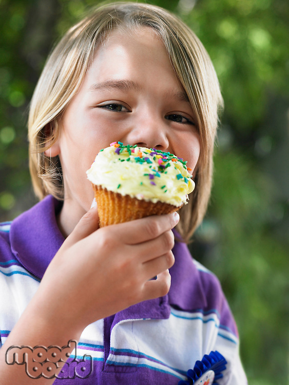 Portrait of young boy (7-9) eating cupcake