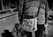 Mao-era communist propaganda on shoulder satchel of a domestic tourist carrying a bounty from a spate of capitalist activity.  Lijiang, Yunnan, China.