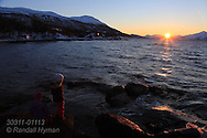 Girl  stands at Telegrafbukta at the south end of Tromsoya island on January 21st watching return of the sun after its two-month absence; Tromso, Norway.