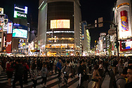 Crowds at the Shibuya crossing surrounded by neon lights in Tokyo, Honshu, Japan