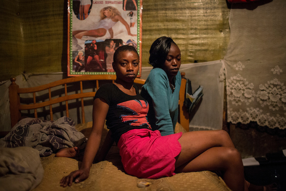 Sex workers Alice, 20 (L) and Claire 17, pose for a photograph as Alice's baby sleeps close by in their home in Kiamaiko, Nairobi, Kenya, June 16, 2015. (For Reuters)