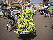 31 JANUARY 2013 - PHNOM PENH, CAMBODIA: A trishaw driver brings a load of bananas into a market in Phnom Penh.   PHOTO BY JACK KURTZ