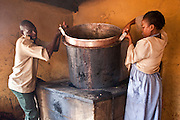Kitchen staff lift off a large pot in the kitchen area of Graissa Road primary school. Their wages are paid by AFCIC (Action for children in conflict). The majority of the 800 pupils are from the Kiandutu slum and many rely on this one meal a day.