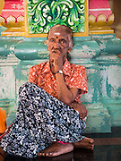 05 JUNE 2015 - KUALA LUMPUR, MALAYSIA:   A woman waits for midday prayers to start in Sri Mahamariamman Temple, the oldest functioning and most important Hindu temple in Malaysia. The principal deity in the temple is Mariamman,  a deity that is popularly worshipped by overseas Indians, especially Tamils, because she is looked upon as their protector during the sojourn to foreign lands. Mariamman is a manifestation of the goddess Parvati, an incarnation embodying Mother Earth with all her terrifying force. She is associated with disease and fever and protects her devotees from unholy or demonic events.    PHOTO BY JACK KURTZ