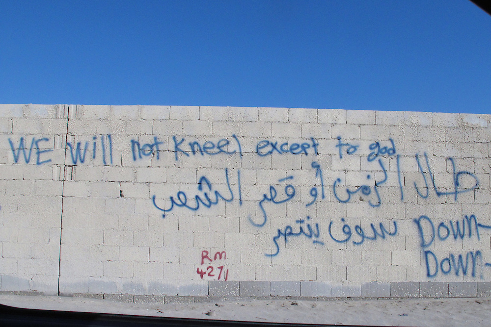 """""""We will not kneel except to God,"""" and in Arabic it reads, """"The time can be long or short, but the people will win"""""""