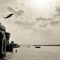 A boy jumps to the ganges' river in Varanasi,  also known as Benares, is a city on the banks of the Ganges (Ganga) in Uttar Pradesh, 320 kilometres (200 mi) southeast of the state capital, Lucknow. It is the holiest of the seven sacred cities in Hinduism and Jainism, and played an important role in the development of Buddhism. Some Hindus believe that death at Varanasi brings salvation.It is one of the oldest continuously inhabited cities in the world and the oldest in India.<br /> The ganges river rising in the Himalayas and emptying into the Bay of Bengal, it drains a quarter of the territory of India, while its basin supports hundreds of millions of people.