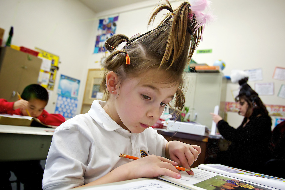 "Natalie Taylor, a first grade student in Joni Thurman's class at Classical Christian Academy, checks her work during Thursday where her class donned their best ""Whoville"" hairdos in honor of Dr. Seuss whose birthday which was Wednesday."