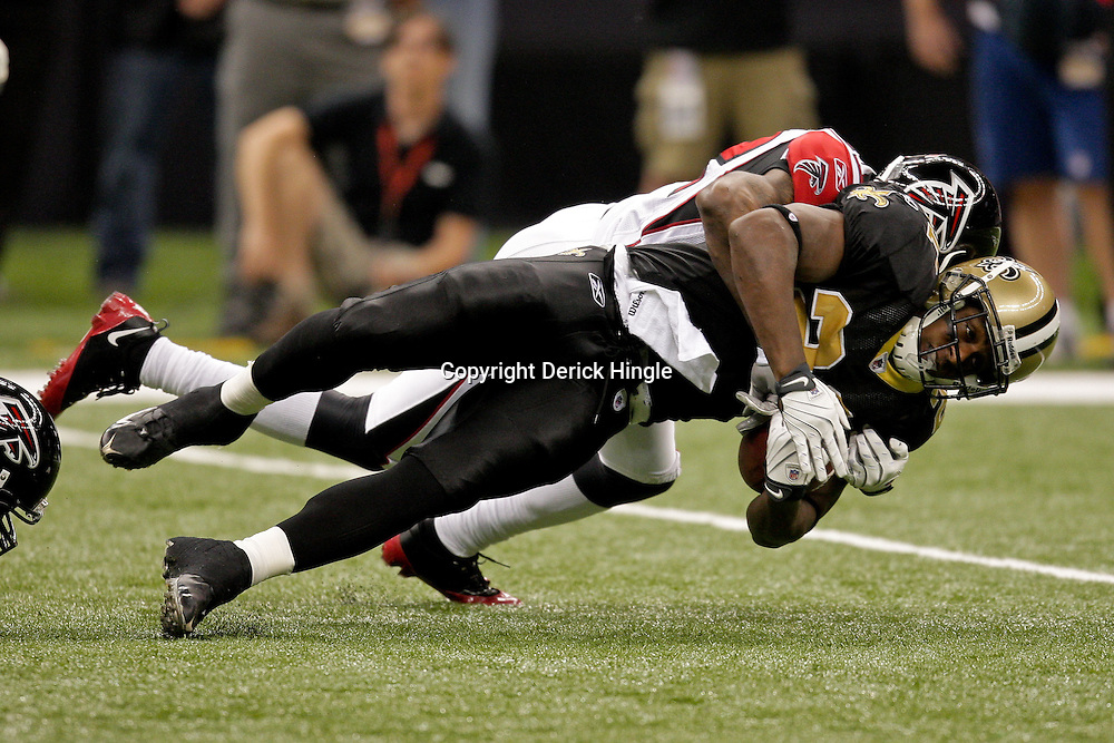 2009 November 02:  New Orleans Saints running back Mike Bell (21) is tackled by Atlanta Falcons cornerback Chevis Jackson (22) during the first quarter at the Louisiana Superdome in New Orleans, Louisiana.