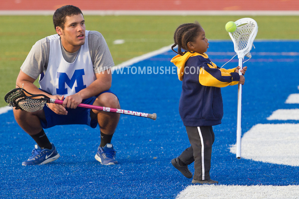 Middletown, New York - A child tries to take a shot with a lacrosse stick as a Middletown High School athlete watches during Faller Field during Family Fun Night on May 17, 2013.