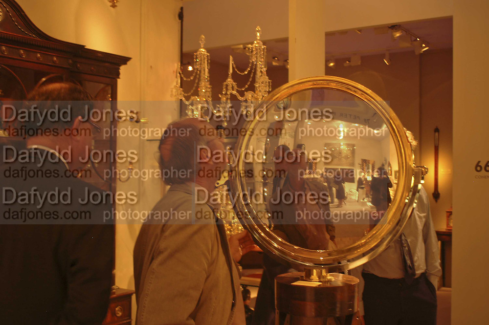Speculum Metal mirror on 'Jeremy' stand. The opening  day of the Grosvenor House Art and Antiques Fair.  Grosvenor House. Park Lane. London. 14 June 2006. ONE TIME USE ONLY - DO NOT ARCHIVE  © Copyright Photograph by Dafydd Jones 66 Stockwell Park Rd. London SW9 0DA Tel 020 7733 0108 www.dafjones.com