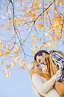 Low angle view of couple hugging against autumn tree