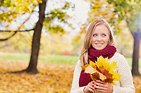 Portrait of beautiful woman holding maple leaves in park