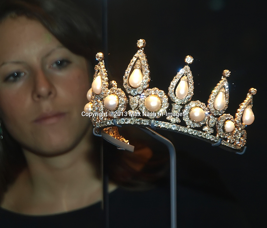 Pearl exhibition in London's V&A museum. <br /> A V&A employee looks at the Roseberry Pearl and Diamond Tiara, at the Pearl exhibition in London's V&A museum. The jewellery belongs to the Qatar Museum, London, United Kingdom. Wednesday, 18th September 2013. Picture by Max Nash / i-Images