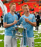 Kevin De Bruyne (17) of Manchester City and Oleksandr Zinchenko (35) of Manchester City hold The FA Cup during the celebrations at full time during the The FA Cup Final match between Manchester City and Watford at Wembley Stadium, London, England on 18 May 2019.