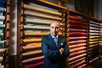 """FLORENCE, ITALY - 26 OCTOBER 2018: Filippo Ricci,  creative director of the eponymous luxury company started by his father, Stefano Ricci, poses for a portrait by the Ermisino fabrics in the showroom of the Antico Setificio Fiorentino, an ancient silk mill he owns in central Florence, Italy, on October 26th 2018.<br /> <br /> The Ermisino is an icon fabric of the ancient silk factory, a special type of Renaissance shot taffeta made with threads of different colours, so as to have tones that are shimmering and fluid like a cascade of light. Woven in three classic weights (leggero, scempio and doppio), for centuries it was the distinctive mark of the most illustrious nobility.<br /> <br /> The Antico Setificio Fiorentino is a silk mill, located in central Florence within view of the old city walls in the San Frediano neighborhood, that produces the kind of fabrics destined for city palaces and country estates. The mill was bought in 2010 by Stefano Ricci from the Pucci, with an eye to using it to produce fabrics for the launch of a new home collection<br /> <br /> Lined up in rows are the dozen looms that take the slender threads, by now dyed emerald and ruby and sapphire, and weave them into the textiles that form a part of the fabric of Florentine life.<br /> <br /> Silk was made in the city as far back as the 1300s, a commodity to trade for precious materials. In more recent times, the fabric in the gowns in """"Il Gattopardo"""" and """"Death in Venice"""" came from the mill, as did much of Maris Callas' wardrobe, robes for Popes, suits for Andre Bocelli, and Nelson Mandela's silk shirts (when he wore one for his audience with Queen Elizabeth II she reportedly remarked, """"that's a beautiful shirt."""") The carmine red curtains at the Villa Medici and the Tribune of the Uffizi were made here. The Presidential Suite at the city's Four Seasons Hotel is decked out in the mill's output, as are the walls of the room of the Czars at the Kremlin, and more than 100 red velvet chairs embla"""