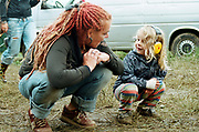 The Free Party and Teknival Scene from the Book 'Out of Order': Woman with dreadlocks talking to to a young girl.