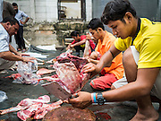 24 SEPTEMBER 2015 - BANGKOK, THAILAND:  Men butcher ritualistically sacrificed sheep during the celebration of Eid al-Adha at Haroon Mosque in Bangkok. Eid al-Adha is also called the Feast of Sacrifice, the Greater Eid or Baqar-Eid. It is the second of two religious holidays celebrated by Muslims worldwide each year. It honors the willingness of Abraham to sacrifice his son, as an act of submission to God's command. Goats, sheep and cows are sacrificed in a ritualistic manner after services in the mosque. The meat from the sacrificed animal is supposed to be divided into three parts. The family retains one third of the share; another third is given to relatives, friends and neighbors; and the remaining third is given to the poor and needy.    PHOTO BY JACK KURTZ