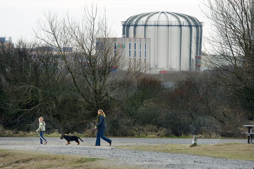 Nederland Petten 7 maart 2009 20090307 Foto: David Rozing ..Kerncentrale Petten, vrouw en kind laten hond uit in duingebied op de voorgrond.  Nuclear reactor for the production of medical isotopes to treat cancer. Nucleaire onderzoeksreactor, de snelle flux reactor In Petten wordt onder meer onderzoek gedaan naar manieren om de levensduur van radioactief afval te verkorten. Daarnaast worden er medische isotopen gemaakt, die gebruikt worden voor kankerbestrijding. Hoge Flux Reactor (HFR) op het terrein is onderzoeksreactor en levert ook radioactieve preparaten aan de medische sector t.b.v. diagnostiek en radiotherarpie (bestraling, radiofarmacie); voorheen Reactor Centrum Nederland (RCN) / Kerncentrale Petten..Foto: David Rozing/