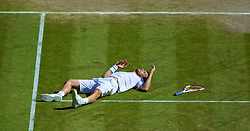 LONDON, ENGLAND - Friday, July 4, 2014: Grigor Dimitrov (BUL) lies prone after falling and losing a point during the Gentlemen's Singles Semi-Final match on day eleven of the Wimbledon Lawn Tennis Championships at the All England Lawn Tennis and Croquet Club. (Pic by David Rawcliffe/Propaganda)
