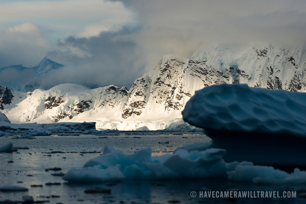 The late evening sun catches the mountains rising sharply on the waterfront of Paradise Harbor, Antarctica.