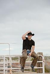 rugged cowboy sitting on a fence