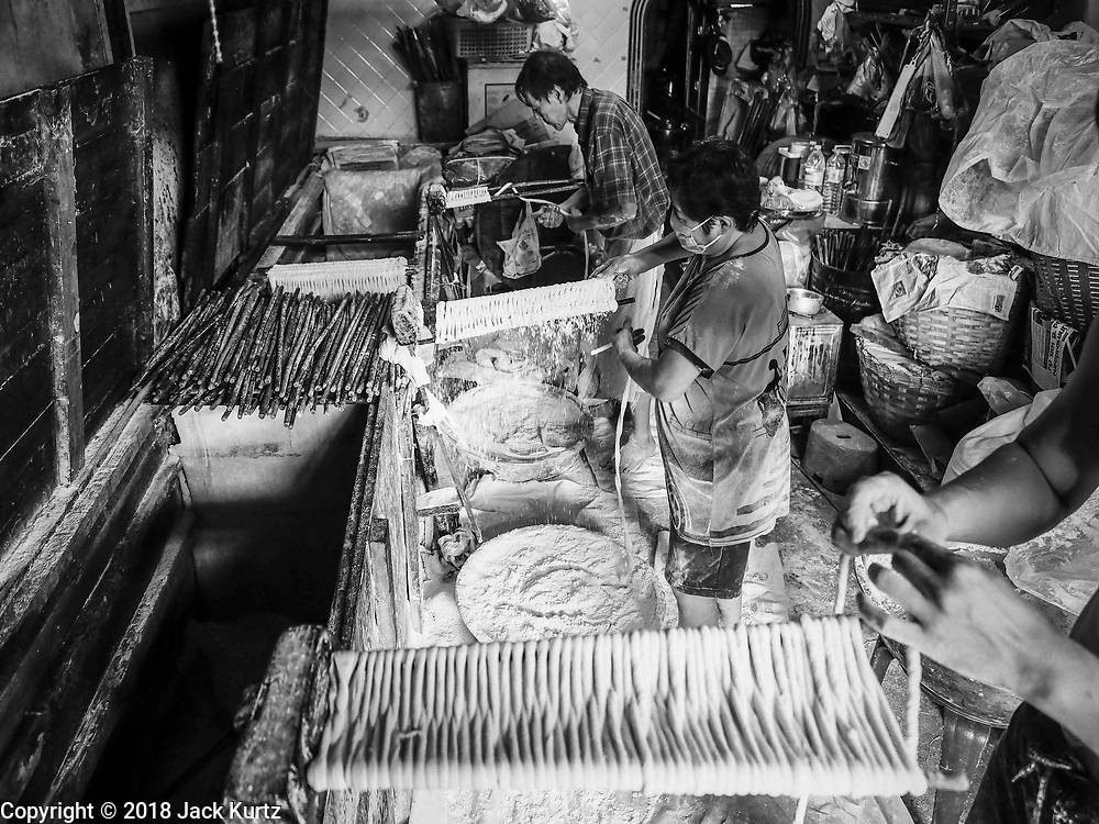 """29 DECEMBER 2018 - BANGKOK, THAILAND: A woman and her husband make longevity noodles in her family shophouse. The family has been making traditional """"mee sua"""" noodles, also called """"longevity noodles"""" for three generations in their home in central Bangkok. They use a recipe brought to Thailand from China. Longevity noodles are thought to contribute to a long and healthy life and  are served on special occasions, especially Chinese New Year, which is February 4, 2019. These noodles were being made for Chinese New Year.      PHOTO BY JACK KURTZ"""