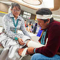 050113       Brian Leddy<br /> Tohatchi High School student Kyrin Harrison helps Miyamura High School student Ashton Francisco rewrap her moccasins during Thursday's Dine Language and Culture Festival at Thoreau High School. The annual event brought in students from all over the district to perform traditional songs and dancing.