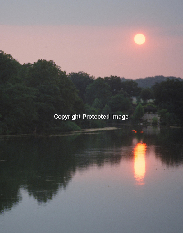 """Sun setting over Lady Bird Lake in Austin, Texas. Vertical. NOTE: Click """"Shopping Cart"""" icon for available sizes and prices. If a """"Purchase this image"""" screen opens, click arrow on it. Doing so does not constitute making a purchase. To purchase, additional steps are required."""