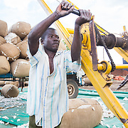 CAPTION: A man works the conveyor belt that takes sacks of raw cotton, as received from the market, to a truck or trailer for weighing and then into the ginnery for processing. LOCATION: Great Lakes Ginnery, Mgabu, Chikwawa, Malawi. INDIVIDUAL(S) PHOTOGRAPHED: Gango George.
