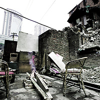CHONGQING - JAN 11 2011: Chairs by the fire in a demolished area near Zhongshan Lu in Yuzhong district. A few families still leave here alongside razed houses and rubble.