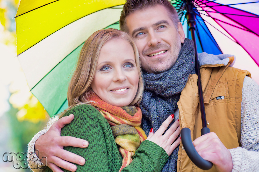 Portrait of attractive man holding umbrella while embracing his wife in park