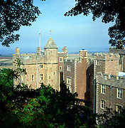Dunster Castle, Somerset, England framed by tree branches