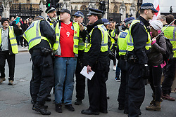 London, UK. 9th March, 2019. Metropolitan Police officers arrest a pro-Brexit activist during a protest by Yellow Vests UK in Parliament Square.