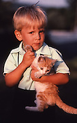 Amish child and cat, portrait on farm,  Lancaster, PA