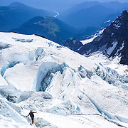 A climber negotiates a ladder placed over a crevasse high on the Ingraham Glacier during a summit of Mount Rainier on June 30, 2015. The iconic Pacific Northwest volcano is a popular challenge for mountaineers.  (Joshua Trujillo, seattlepi.com)
