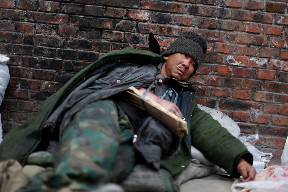 A homeless man with a broken arm lies at an alley where petitioners live as they wait to have her case seen by the petitions office in  Beijing, China, Tuesday, March 3, 2009. Many Chinese have come from around the country to Beijing seeking redress for problems with local officials, flocking to the capital to coincide with the annual National People's Congress session. Their numbers commonly increase ahead of the meeting, and they are often followed by local police to the capital and taken back home.