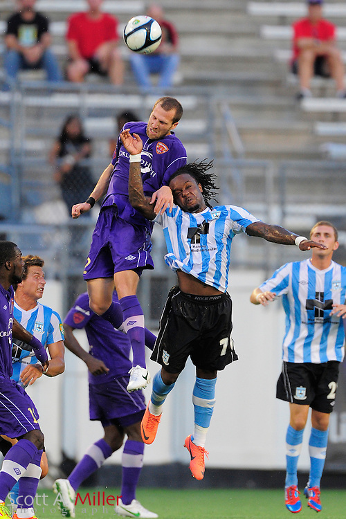 Orlando City Lions defender Rob Valentino (22) and Wilmington Hammerheads forward Chukwudi Chijindu (70) go airborne for a ball during their game at the Florida Citrus Bowl on July 25, 2012 in Orlando, Florida. ..©2012 Scott A. Miller