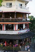 Phnom Penh, Cambodia. Tourists having a sundowner and watching evening rush hour from River Crown Restaurant and Bar.