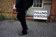 A businessman/commuter waslks past St. Saviour's Church, Herne Hill SE24 that serves as a temporary Polling station for voters on Britain's general election day.
