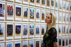 © Licensed to London News Pictures. 11/11/2019. London, UK. A staff member views the preview of 'Steve McQueen Year 3' exhibition at Tate Britain. An installation of over 3,000 class photographs on the walls of Tate Britain's Duveen Galleries, depicting more than 70,000 Year 3 pupils from London's primary schools by Turner Prize-winning artist and Oscar-winning filmmaker Steve McQueen. The exhibition opens on 12 November until 3 May 2020. Photo credit: Dinendra Haria/LNP