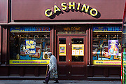An elderly woman walks past a Cashino amusement arcade in Lewisham, London, United Kingdom.