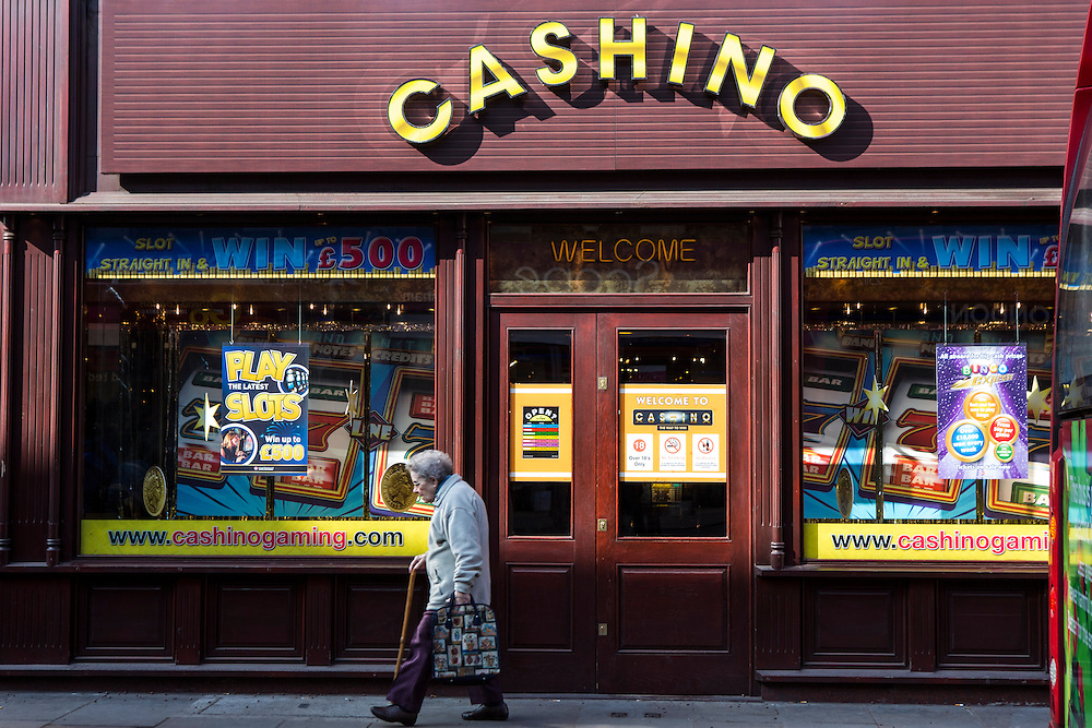 An elderly woman walks past a Cashino amusement arcade in Lewisham, London, United Kingdom.