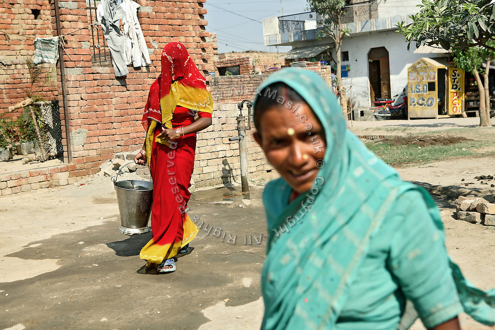 Women are collecting water contaminated with heavy metals and pesticides from a hand-pump on the streets of Jaibheem Nagar, pop. 10000, a large slum located near the banks of the Kali river (East), Meerut District, Uttar Pradesh, India, on Sunday, Mar. 16, 2008.