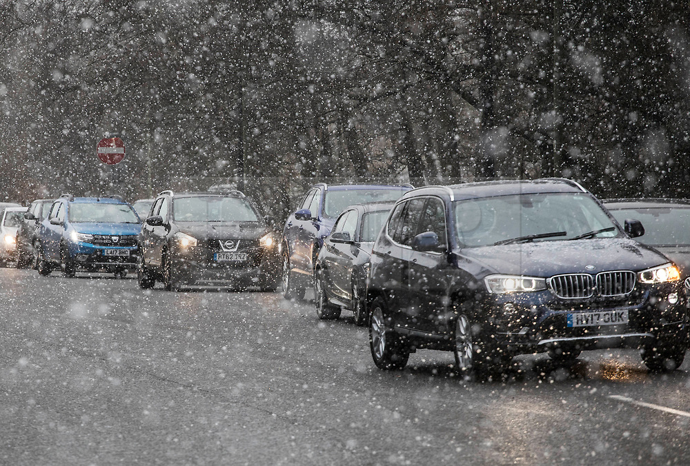 © Licensed to London News Pictures. 26/02/2018. Oxshott, UK. Traffic is seen as snow flurries begin to settle as a cold front sweeps in from the east - with heavy snow expected later in the week in parts of the UK. Photo credit: Peter Macdiarmid/LNP